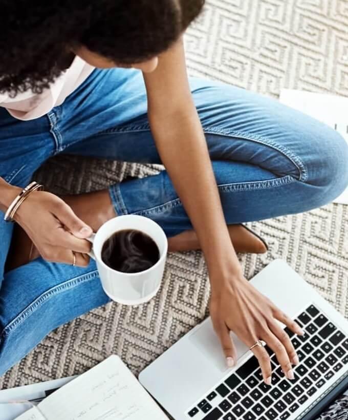 Woman sitting on floor with coffee in hand working on computer